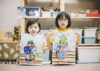 2 asian chinese children displaying their painting after the class at the art center looking at the camera